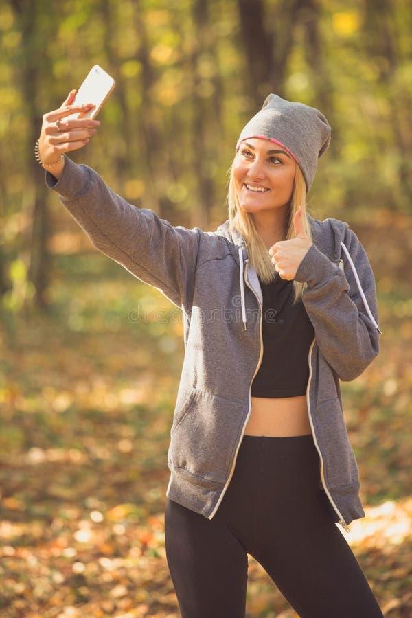 Flickan i skogen gör en selfie och visar upp hennes tumme fotografering för bildbyråer