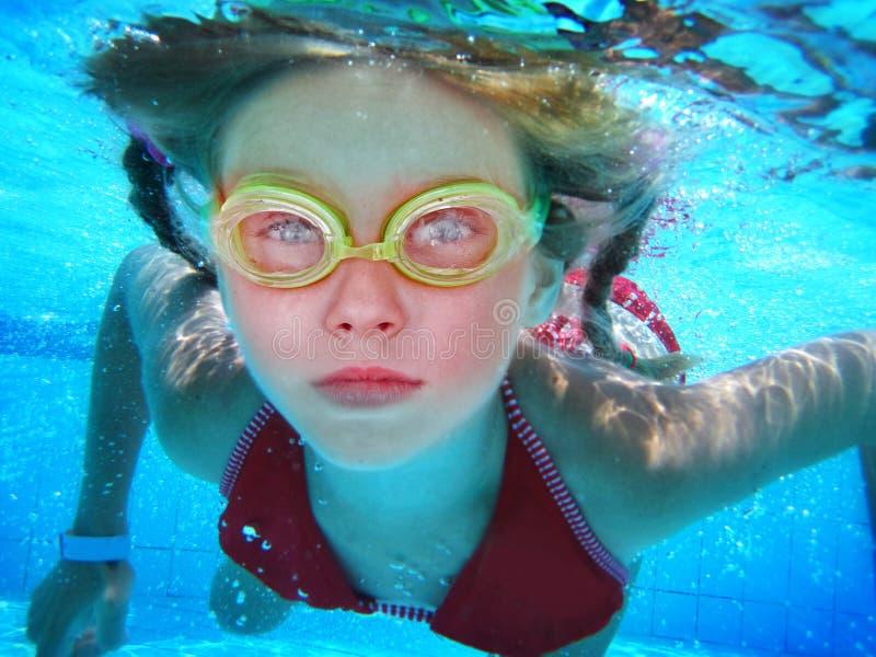 Flickan i skyddsglas?gon simmar och dyker under vatten royaltyfri foto