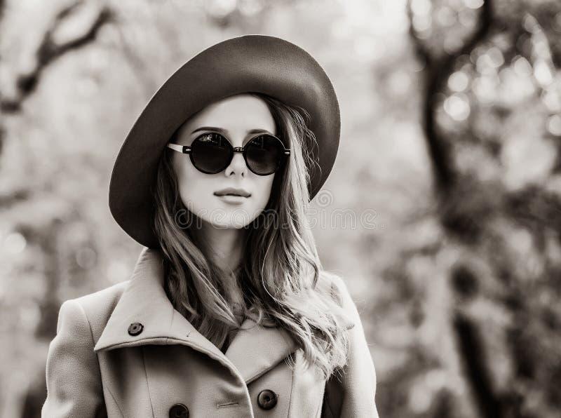 Flickan i solglasögon och hatten i hösten parkerar royaltyfria bilder