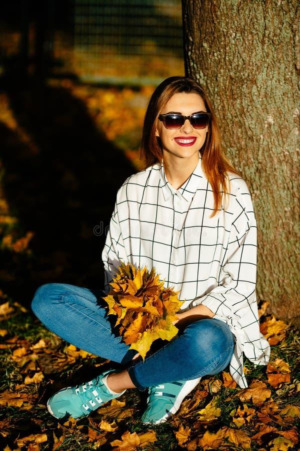 flickan i solglasögon som sitter under trädet i höst, parkerar arkivbild