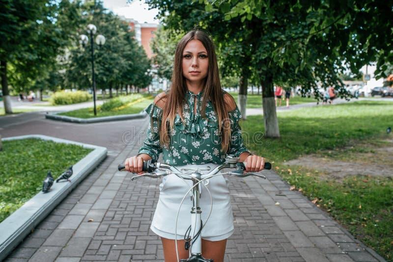 Flickan i sommaren parkerar in ställningar med en cykel i staden Bakgrundsgångbanaträd Gå den aktiva livsstilen på royaltyfria foton