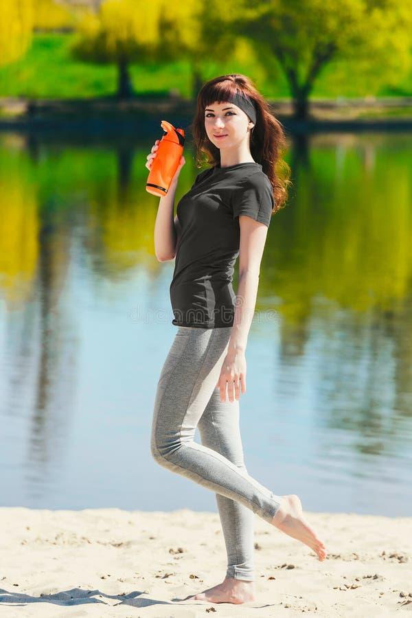 Flickan i sportkläder rymmer en flaska av vatten och att se bort och att le som står på stranden efter genomkörare royaltyfri bild
