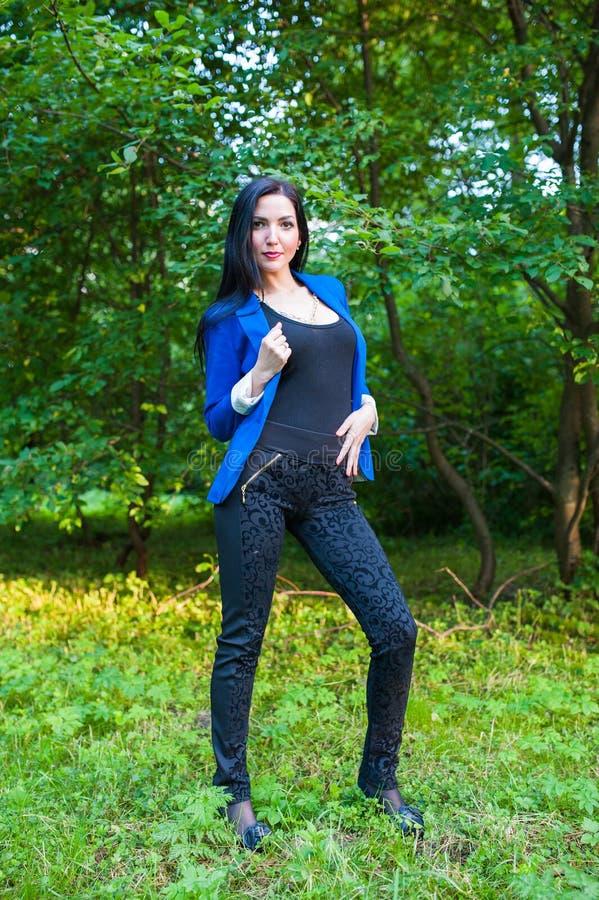 Flickan i svart på bakgrunden av naturen Stående oavkortad tillväxt som poserar för kameran arkivfoton