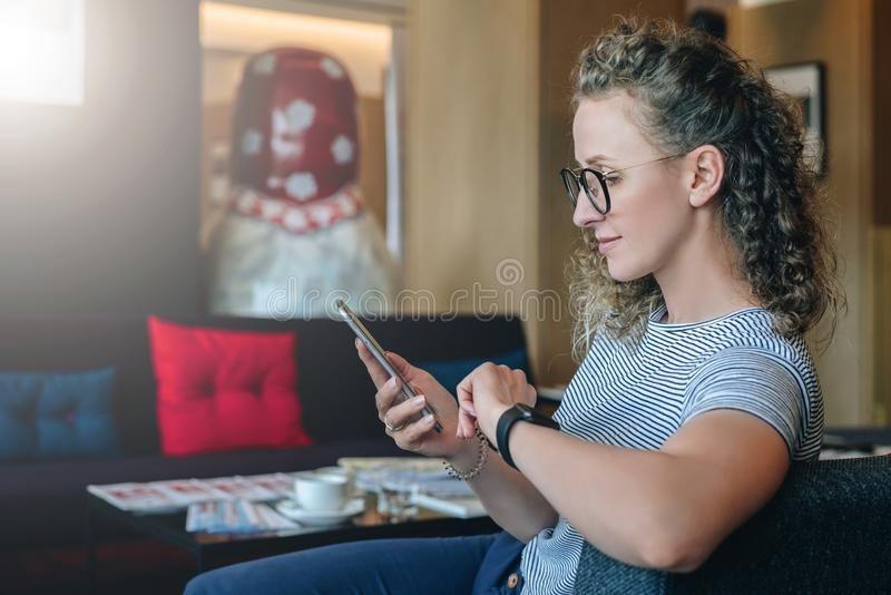 Flickan i t-skjorta är prata och att blogging som kontrollerar emailen Student som lär och att studera Online-marknadsföring, utb royaltyfri fotografi