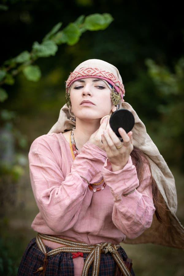 Flickan i tappningkläder gör makeup royaltyfri bild