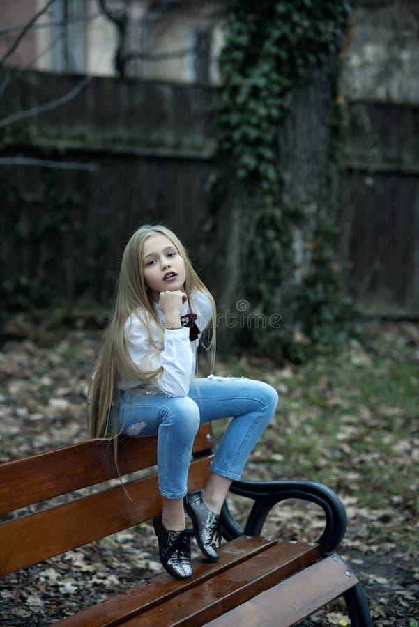 Flickan i trendig jeans sitter p? b?nken, mode Sm?barn med l?ngt blont h?r, utomhus- sk?nhet f?r frisyr Behandla som ett barn sk? royaltyfri fotografi