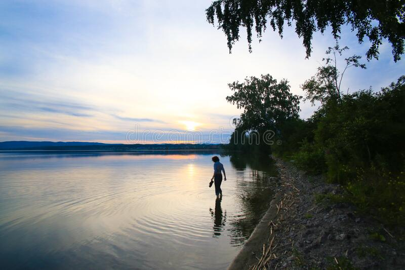 Flickan i vattnet nära sjön arkivfoto