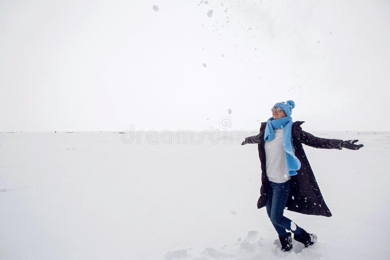 Flickan i vinter beklär anseende på en djupfryst sjö royaltyfria bilder
