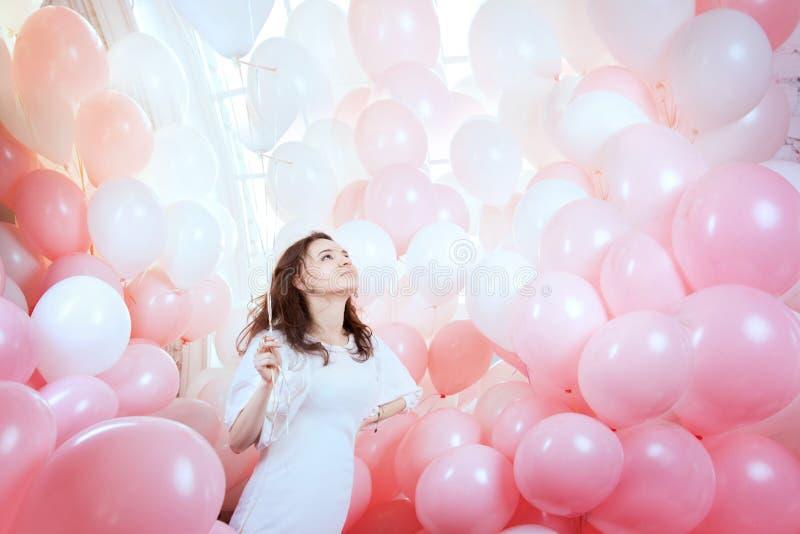 Flickan i vit flyger bland rosa ballonger royaltyfri fotografi