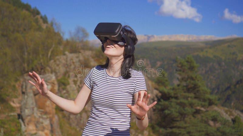 Flickan i vr med exponeringsglas ler, medan stå utomhus i bergen fotografering för bildbyråer