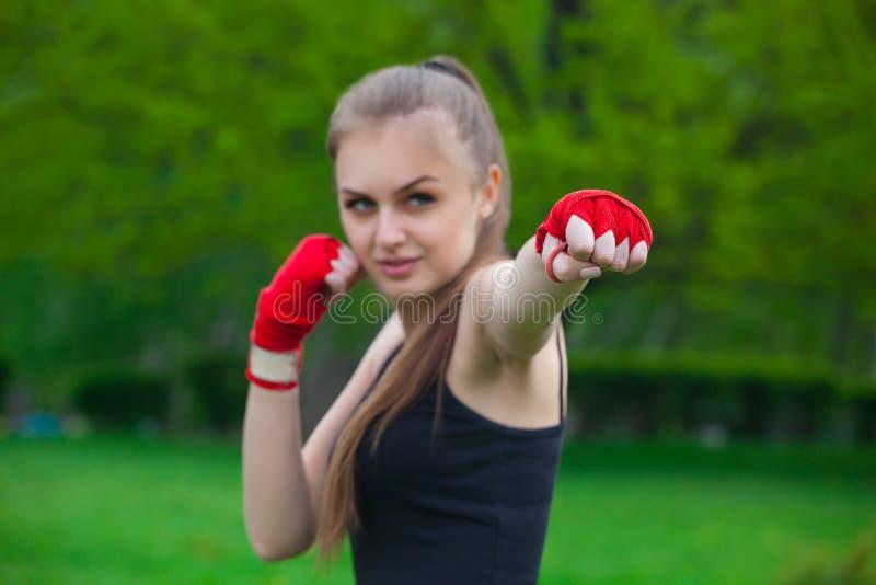 Flickan idrottsman nen, boxaren, i parkera ger också handen som är komprimerad i en näve framåtriktat med de reeled sportarna som arkivbilder
