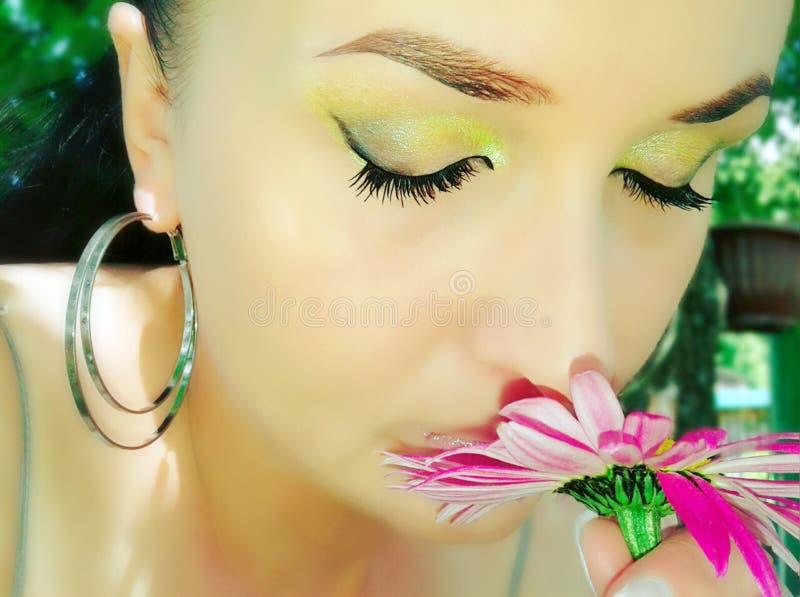 Flickan inhalerar doft av blommor royaltyfri bild