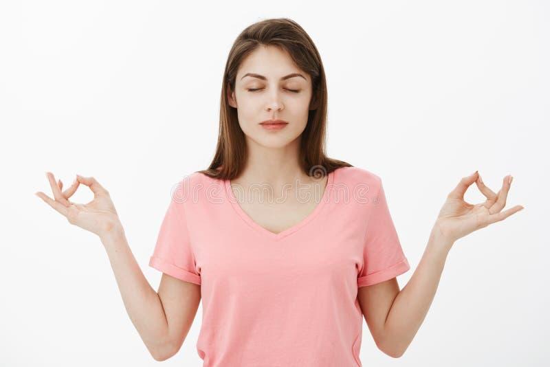 Flickan inhalerar luft och kopplar av Stillhet och lättad attraktiv ung kvinna i den rosa t-skjortan som står med stängda ögon oc arkivfoto