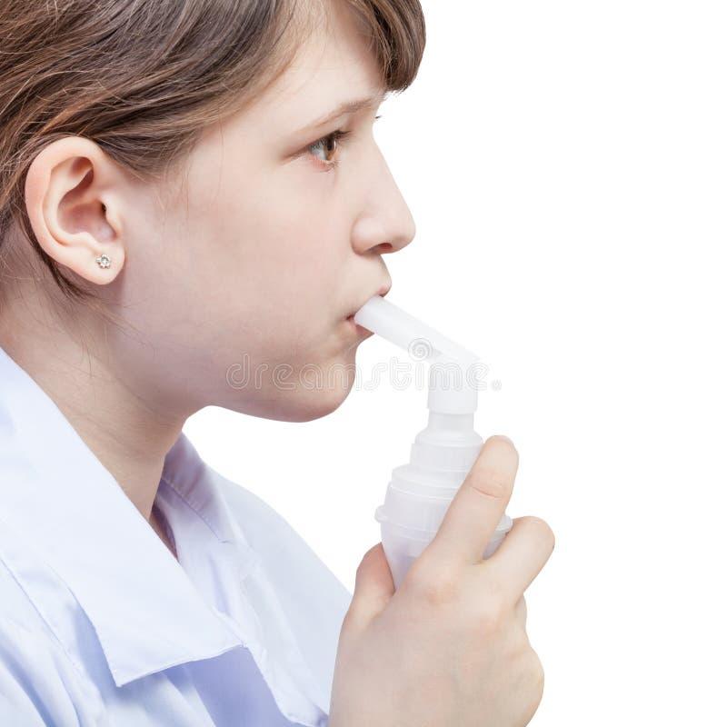 Flickan inhalerar med munstycket av strålnebulizeren royaltyfri foto