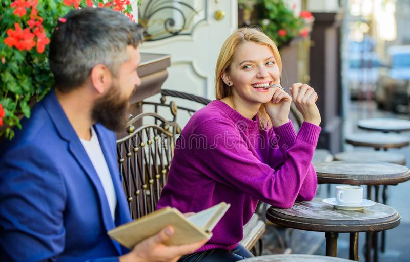 Flickan intresserade vad han läste Möte av folk med liknande intressen Mannen och kvinnan sitter kaféterrassen Gemensam litteratu royaltyfri foto