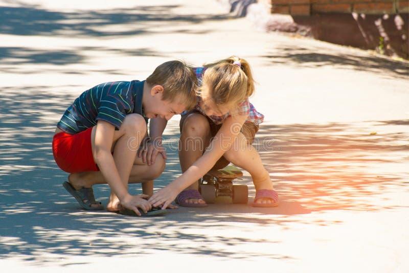 Flickan känner sig ledsen för pojken, hennes broder, som sårades, medan rida en skateboard på en väg i gatan arkivbilder