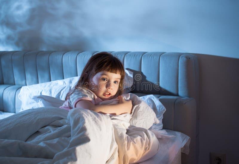 Flickan känner skräcken, medan ligga i säng royaltyfria foton