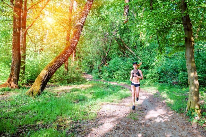 Flickan kör i skogen royaltyfria foton