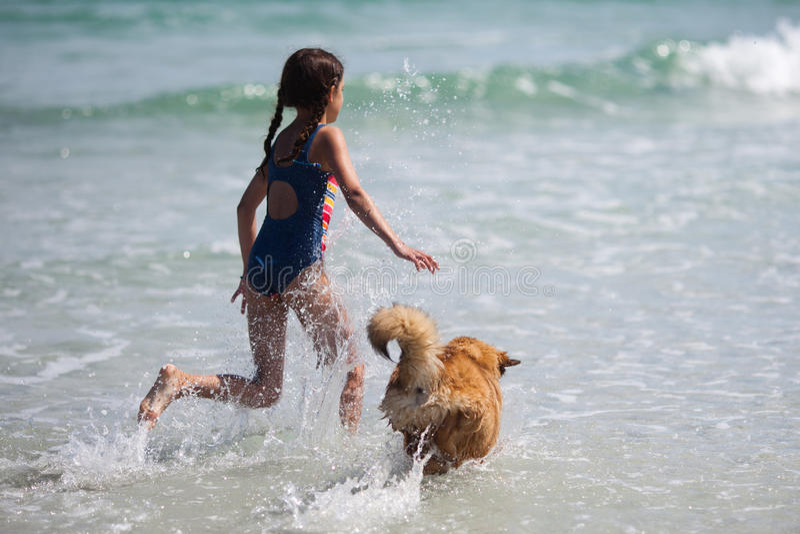 Flickan kör med en hund till och med vattnet royaltyfri bild