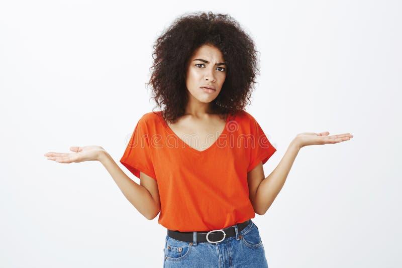 Flickan kan inte få vad pojkvännen önskar Stående av den korkade upprivna attraktiva mörkhyade kvinnan med den afro frisyren arkivfoton