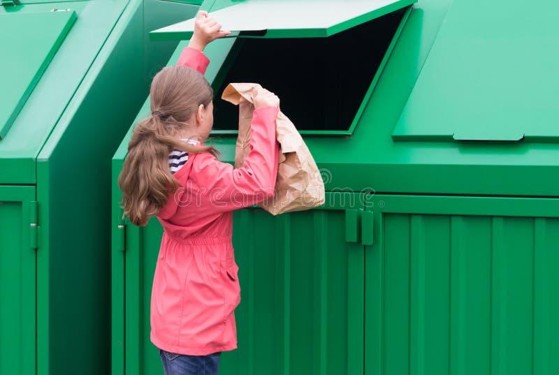 Flickan kastar ut en pappers- påse i en grön dumpster royaltyfri fotografi