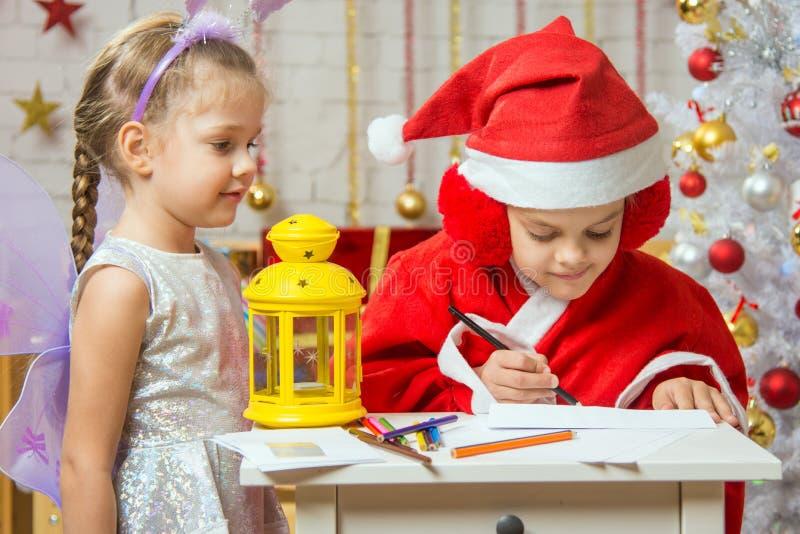 Flickan klädde, som Santa Claus undertecknar kuvertet med en bokstav och att stå bredvid en flicka som kläs som feer arkivbild