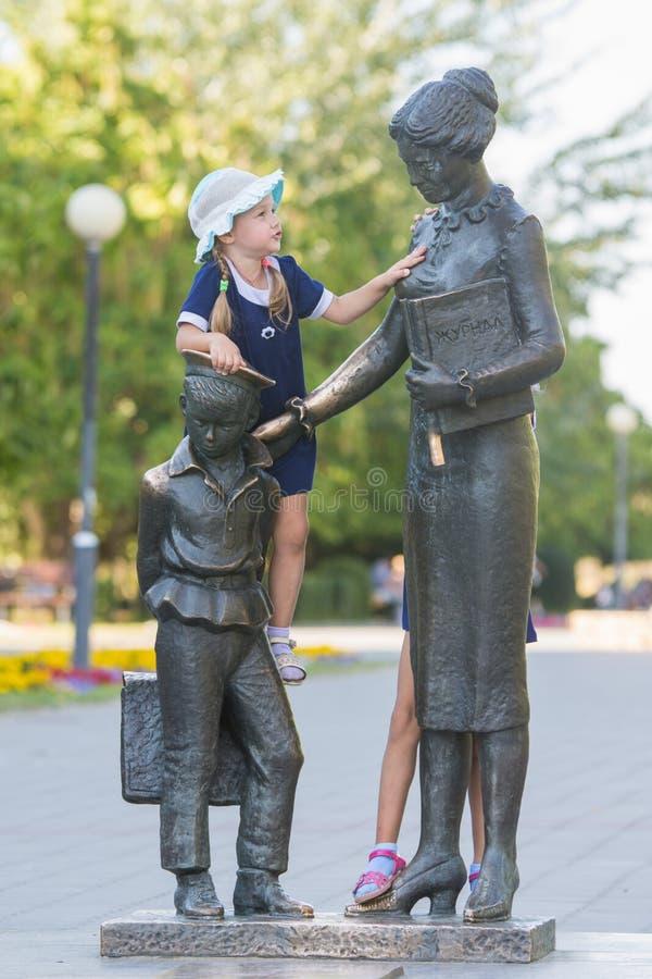 Flickan klättrade på monumentet till den första läraren royaltyfria foton