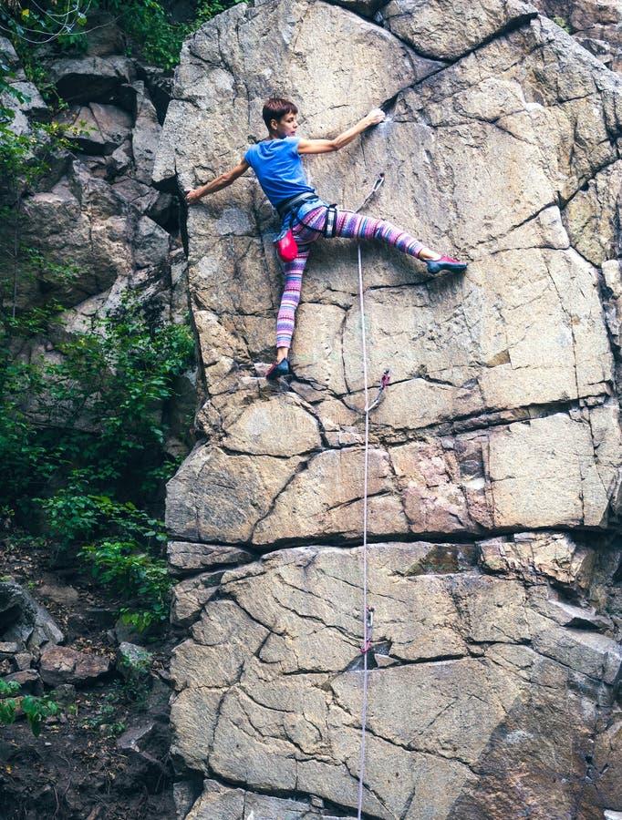 Flickan klättrar graniten vaggar royaltyfria foton