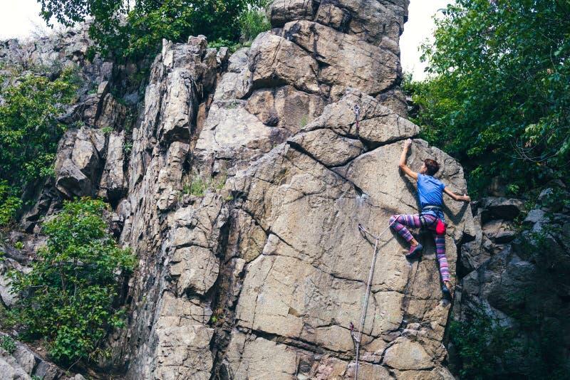 Flickan klättrar graniten vaggar arkivbilder