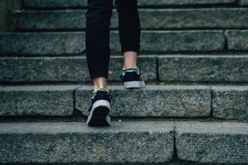 Flickan klättrar på konkret trappa arkivbild