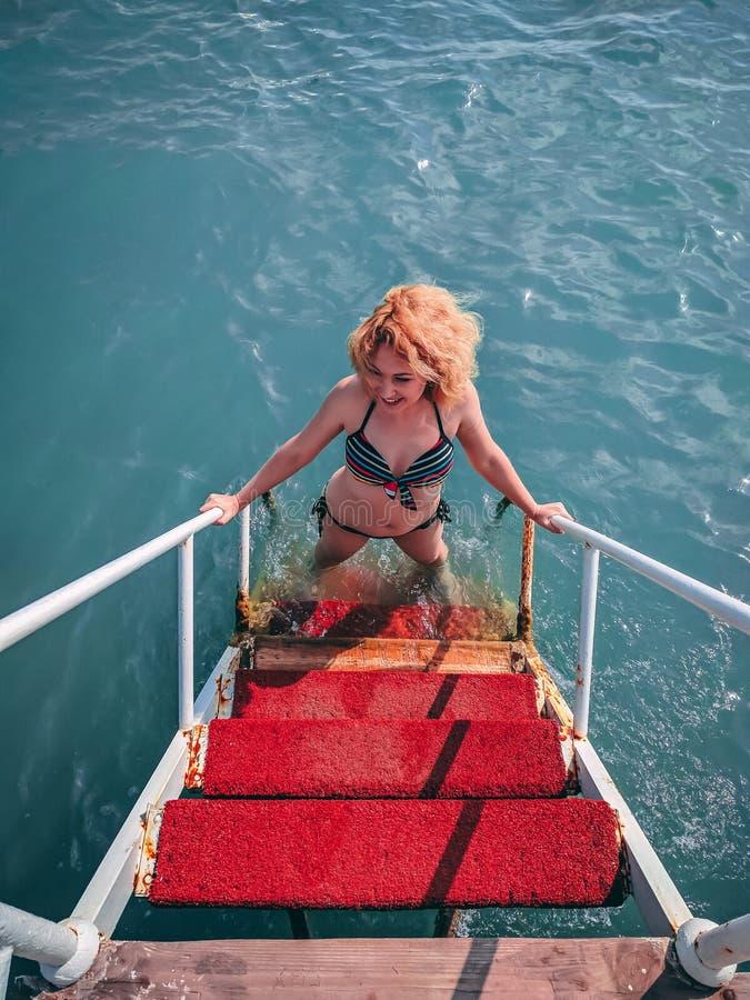 Flickan klättrar röd trappa arkivfoton