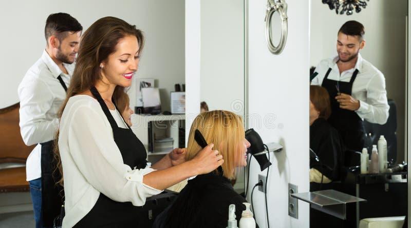 Flickan klipper hår på hårsalongen royaltyfria bilder