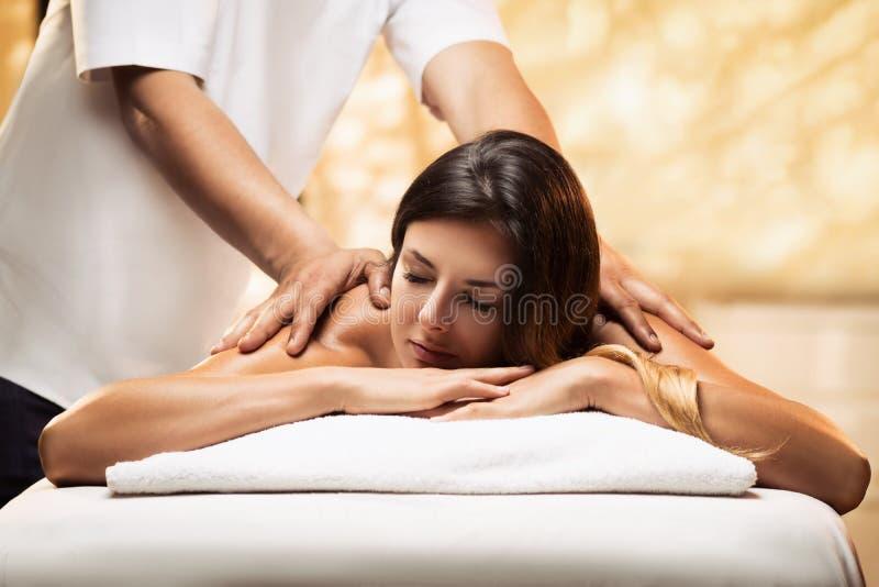 Flickan kopplar av i en brunnsortsalong och får massage royaltyfria bilder