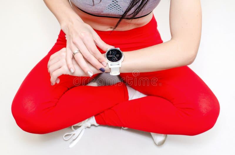 Flickan korsade ben i röd sportdamasker, blickar på performaen arkivbilder
