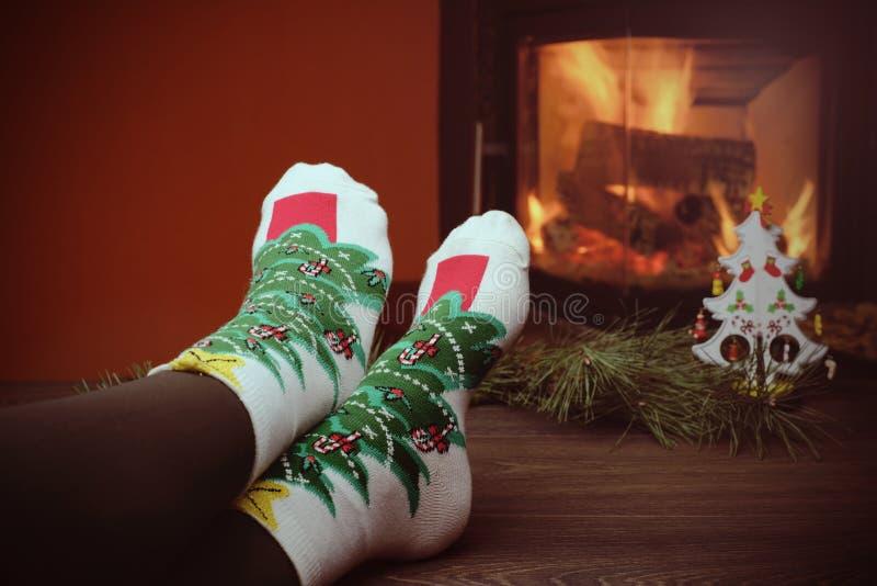 Flickan lägger benen på ryggen i sockor nära spisen med lite julträdet arkivfoto