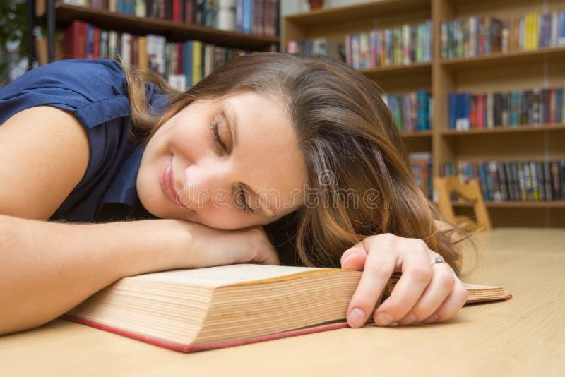 Flickan lägger ner på en bok i arkivet och leendena som har stängt hennes ögon arkivfoton