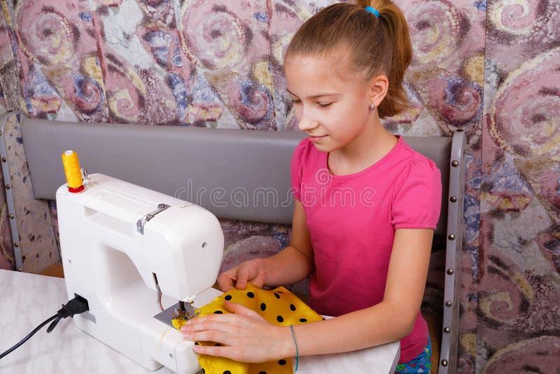 Flickan lär att sy arkivfoto