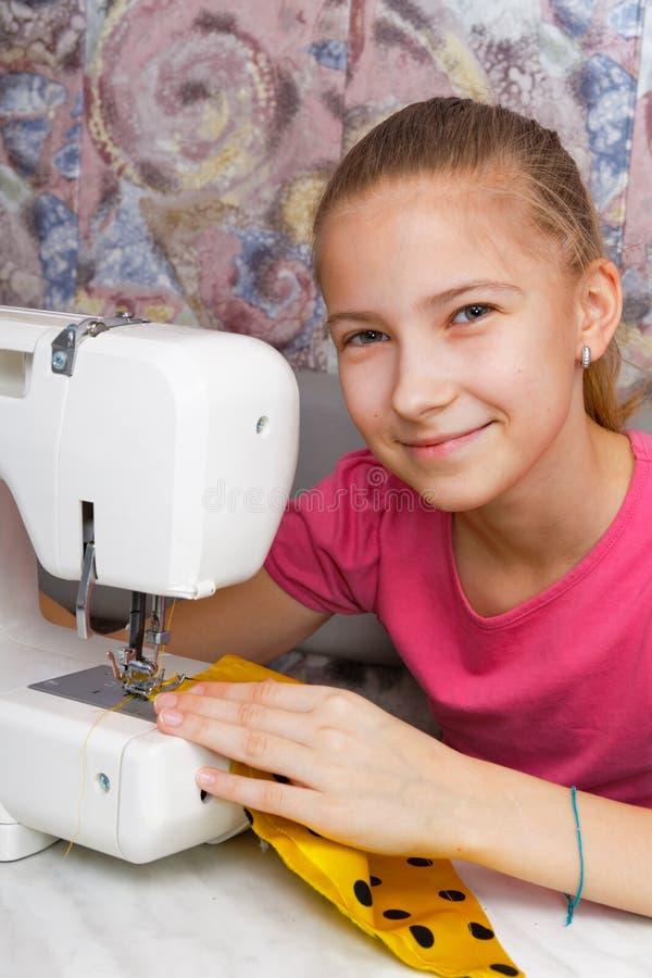 Flickan lär att sy på en symaskin royaltyfri fotografi