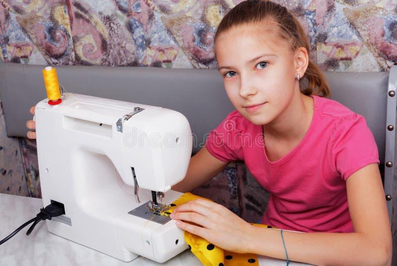 Flickan lär att sy på en symaskin royaltyfri bild