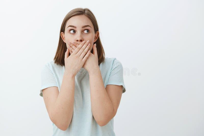 Flickan lär den chockerande hemliga försökande uppehället det Stående av den chockade och förvånade bekymrade mållösa kvinnabeläg royaltyfri fotografi