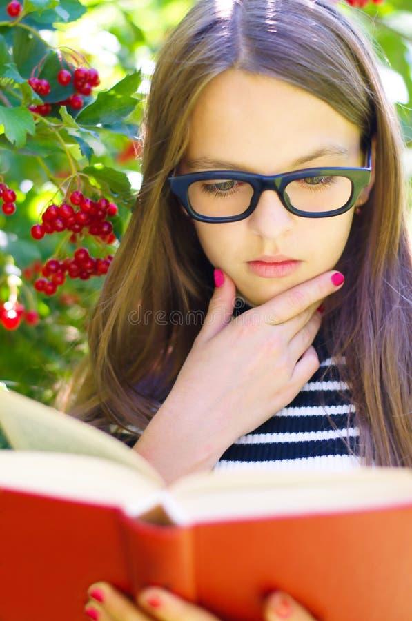 Flickan läser en bok arkivfoton