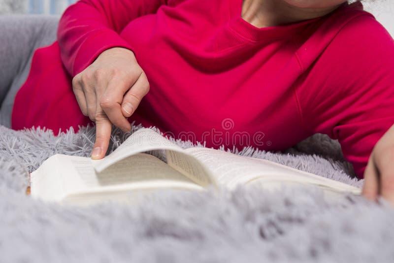 Flickan läser Händer och boknärbild Begreppet av läsning En ung kvinna läser en roman Läs en stor bok arkivfoto