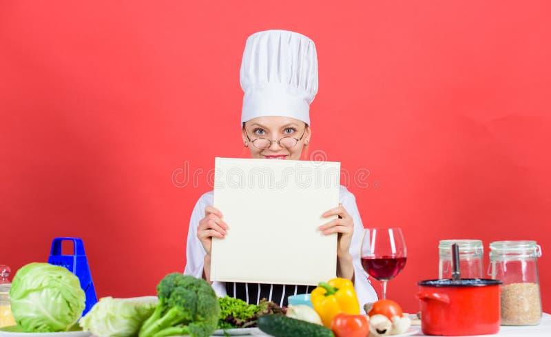 Flickan l?ste b?sta kulinariska recept f?r bok Kulinariskt skolabegrepp Bok vid ber?mt kockkopieringsutrymme Yrkesm?ssig niv? Kvi arkivbilder