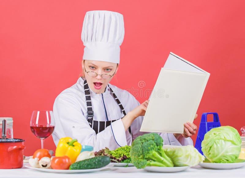 Flickan l?ste b?sta kulinariska recept f?r bok Kulinariskt utbildningsbegrepp Kvinnlign i hatt och förkläde vet allt omkring royaltyfri fotografi