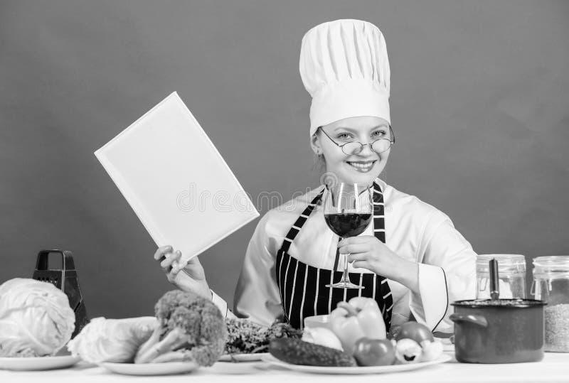 Flickan l?ste b?sta kulinariska recept f?r bok?verkant traditionell kokkonst Kulinariskt skolabegrepp Kvinnlign i hatt och f?rkl? royaltyfria bilder