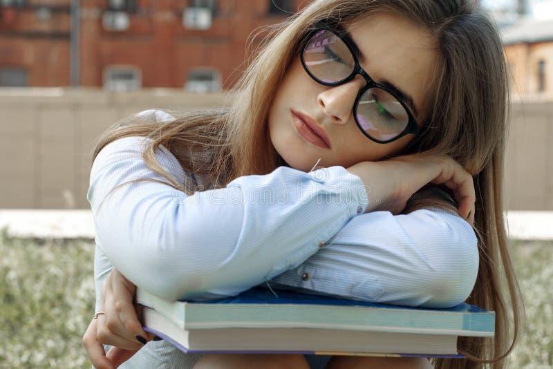 Flickan lade hennes huvud på böckerna fotografering för bildbyråer