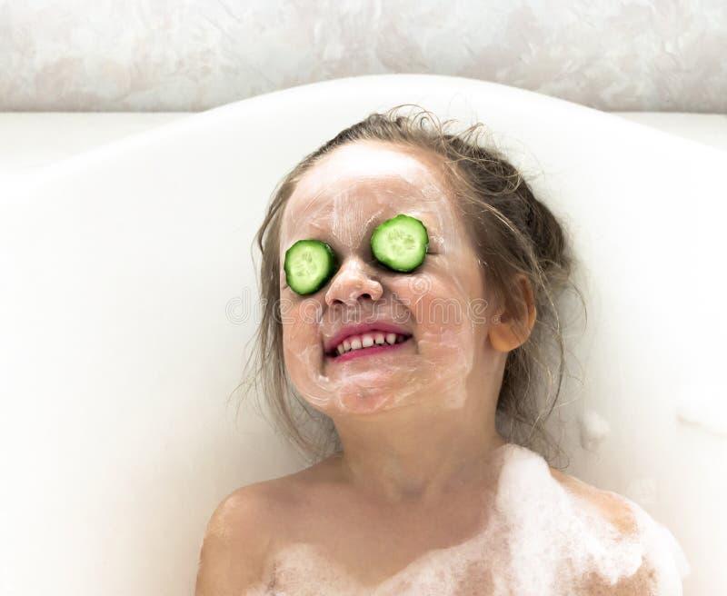 Flickan ler ett snövitt leende i badrumframsidan som rappas med vitkräm, och ögonen är en gurka royaltyfri bild