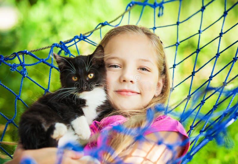 Flickan ligger i en hängmatta med en katt i den öppna luften royaltyfria foton