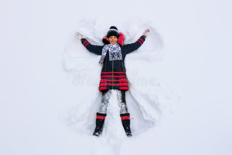 Flickan ligger i snön och gör en snöängel royaltyfri foto
