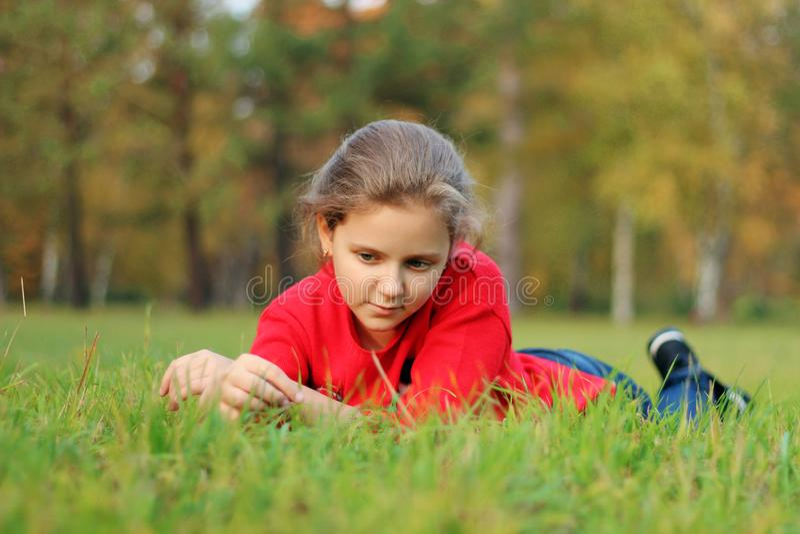 Flickan ligger på det gröna gräset i parkera royaltyfria foton